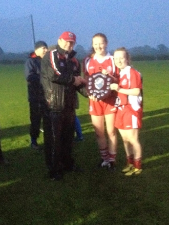 TOMAS GOGGIN INCH ROVERS SECRETARY & EAST CORK BOARD CHAIRMAN PRESENTING THE SHIELD TO JOINT CAPTAINS ROSE GOGGIN & AOIFE HIGGINS
